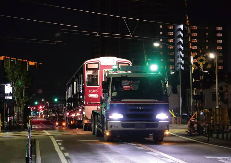 夜の道路を輸送される阪急電車
