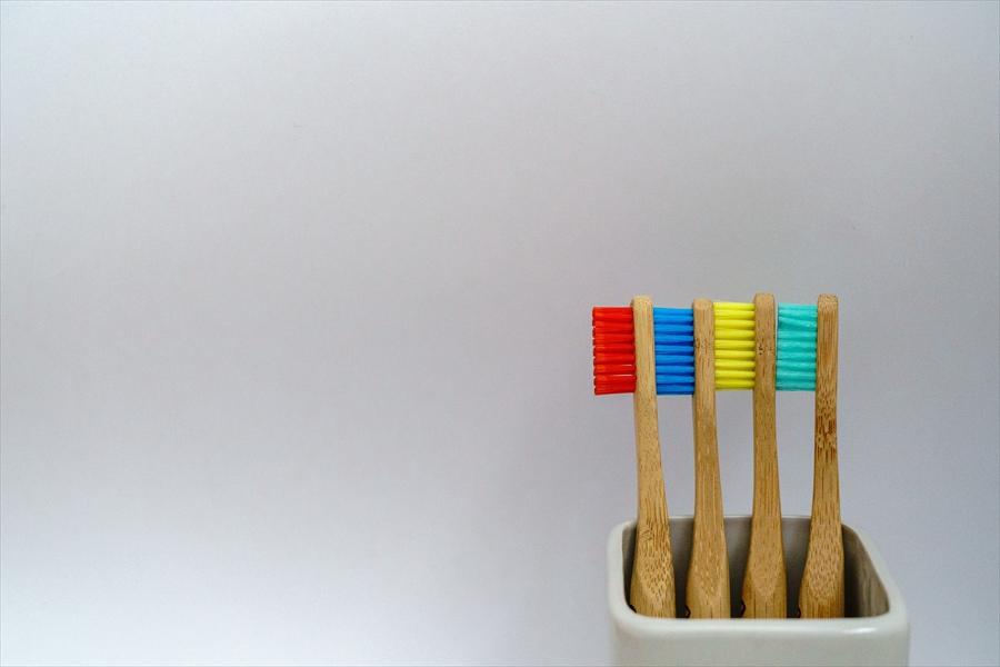 持ち手が木で出来た赤青黄緑の4本の歯ブラシ