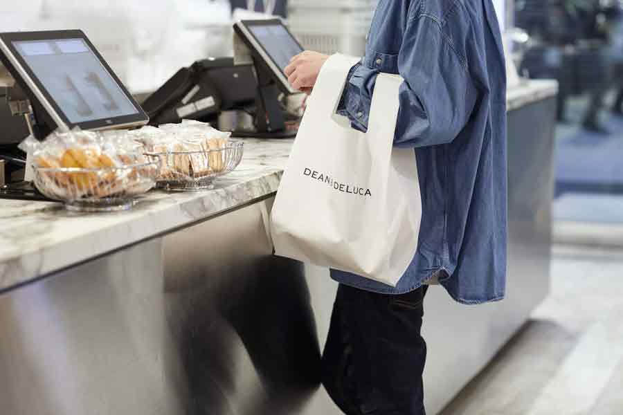 DEAN & DELUCAのエコバッグを持ったレジ前の女性