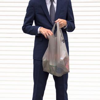 エコバッグを使うスーツを着た男性