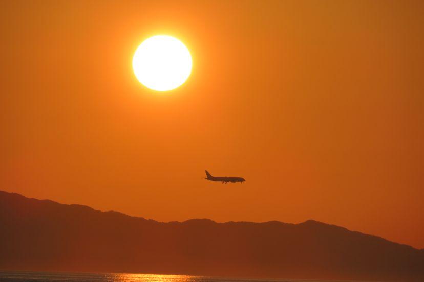 夕陽の下を飛ぶ飛行機