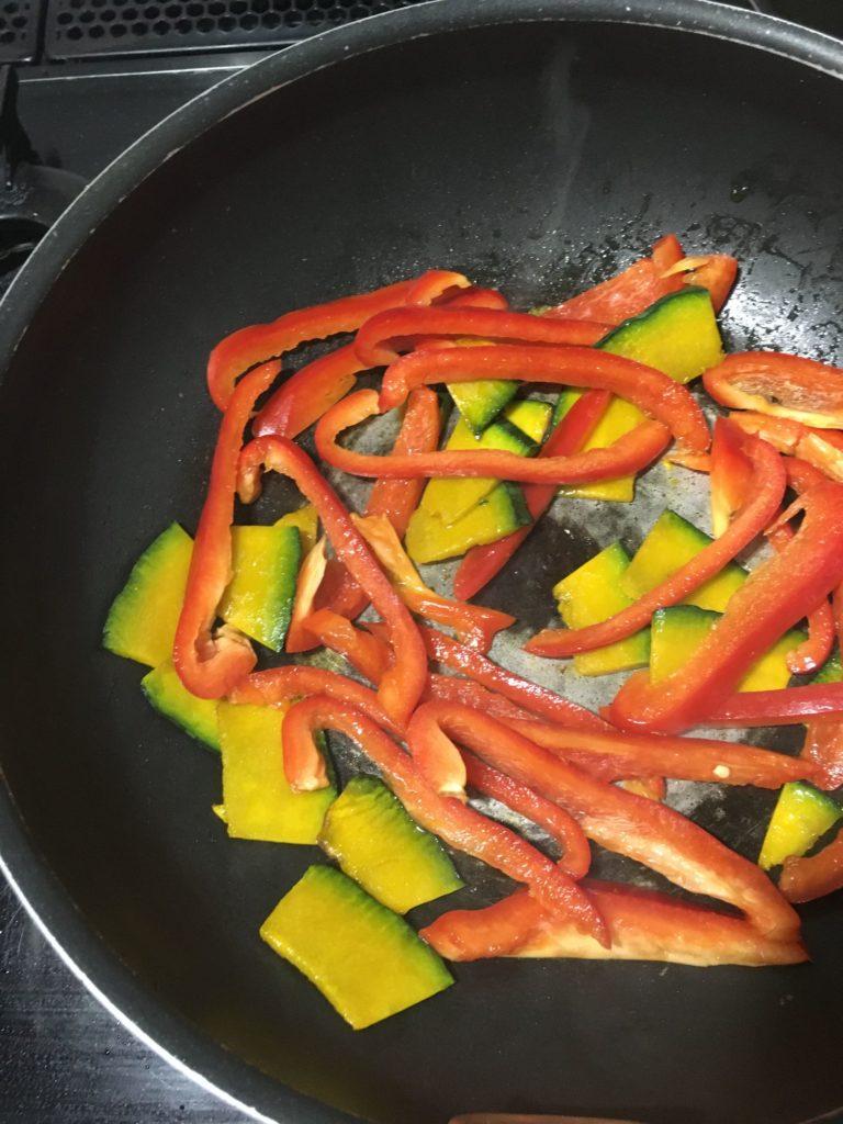 少量の油で炒めているパプリカとカボチャ