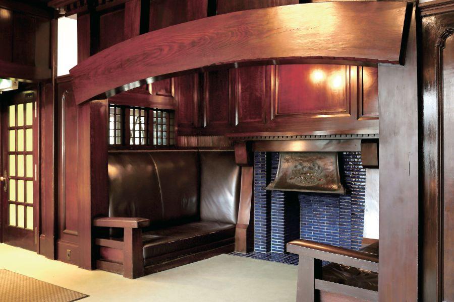 玄関脇に設置された、造り付けの革張りソファと暖炉