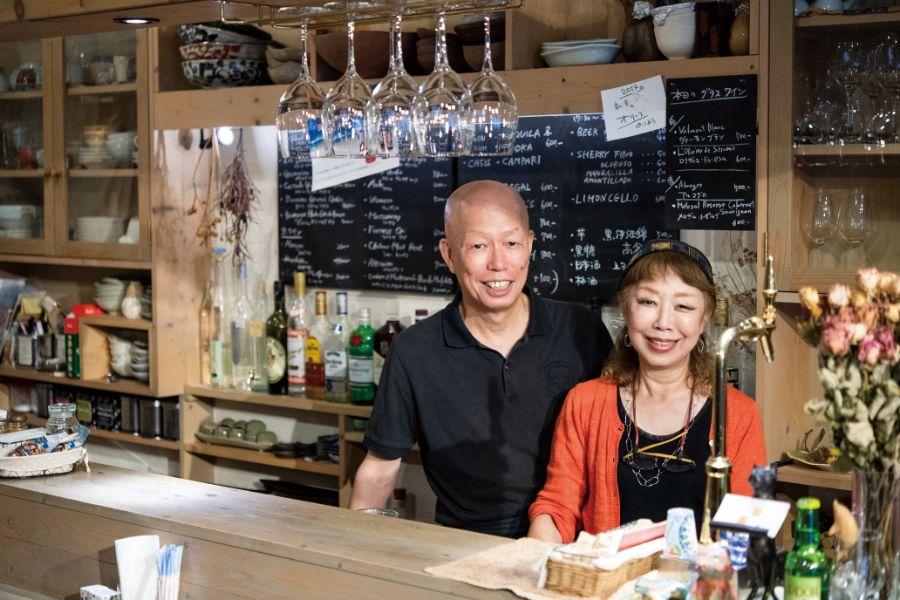 店のカウンターでほほ笑む田中隆夫さん 明美さんご夫妻