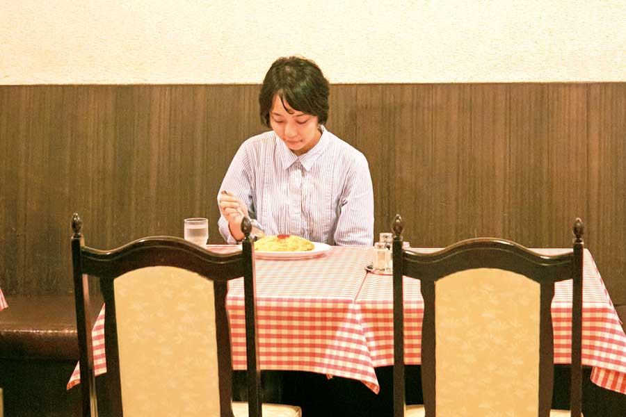 十字屋で料理を食べる女性