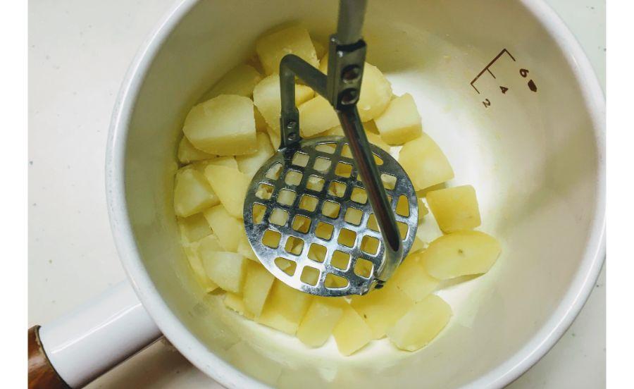 茹でたジャガイモをマッシュしている