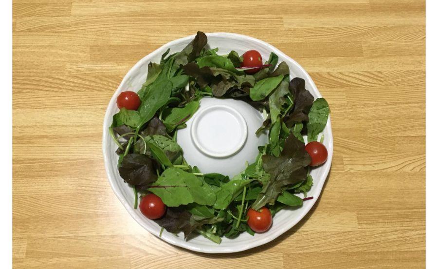丸いお皿のうえにリーフサラダを盛っている