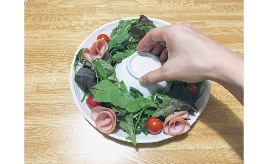リースに見えるサラダを作っている