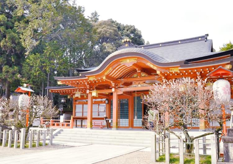 朱色の社殿と脇の梅