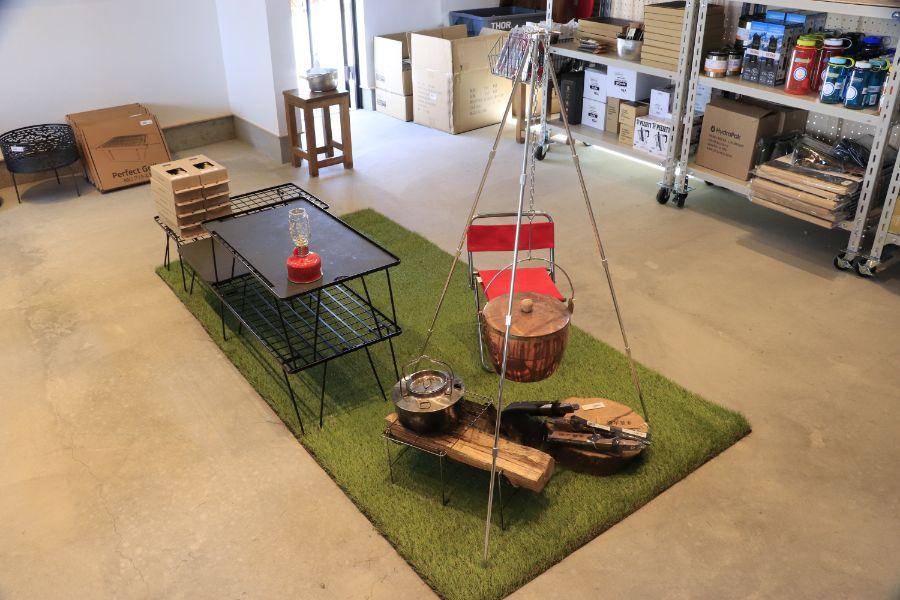 テーブルや鍋、ケトルなどのアウトドア用品の展示