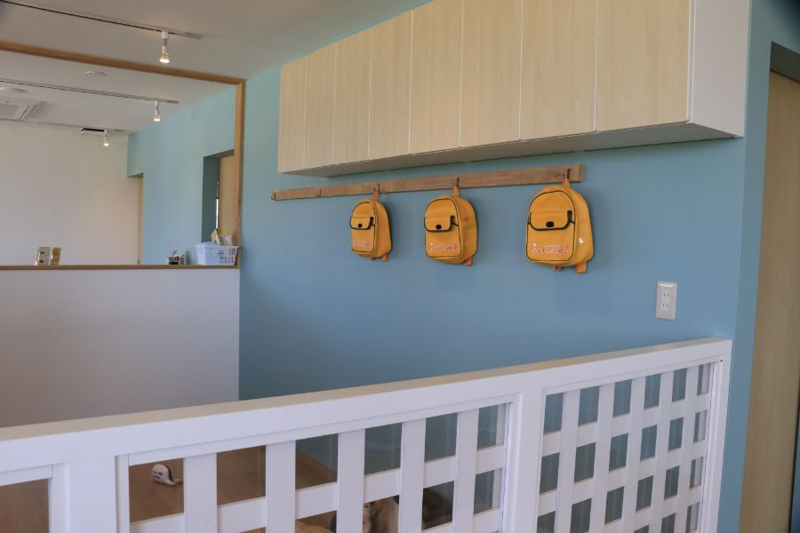 幼稚園の壁にかかる黄色いリュック
