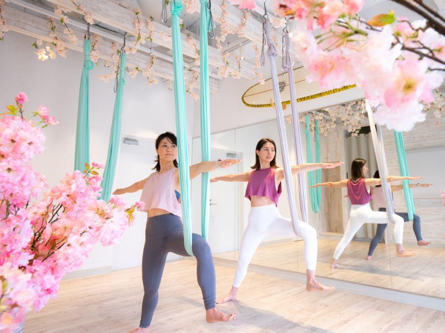 桜の装飾のスタジオでヨガをする女性