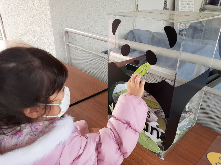 パンダのボックスにメッセージカードを入れる子ども