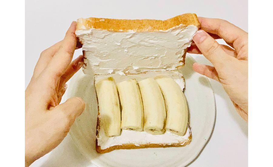 生クリームをぬった食パンの上にバナナを並べたところに食パンを乗せているところ