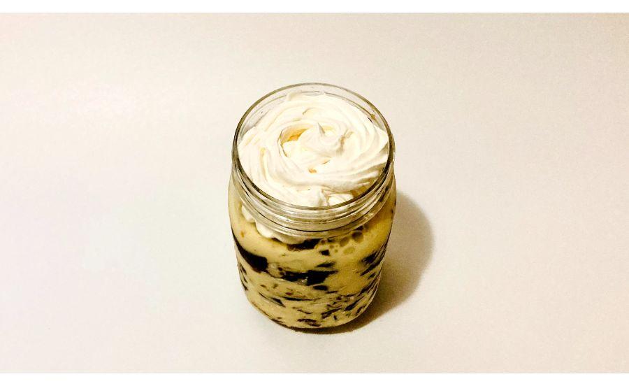 容器に入れたコーヒーゼリーとアイスクリームを蓋の手前まで何層にも重ねたものの上にホイップをしぼった状態