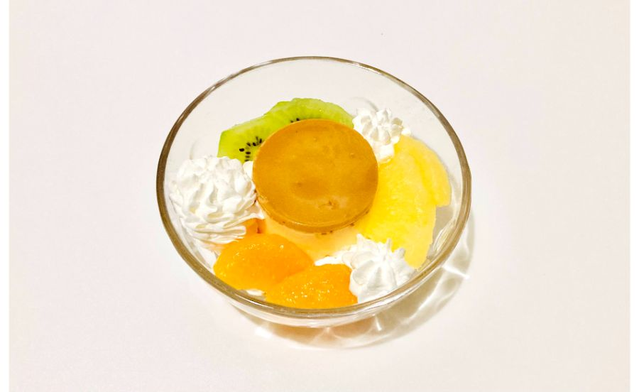 器に出した焼きプリンにホイップクリームを絞ったものにフルーツを盛り付けたもの